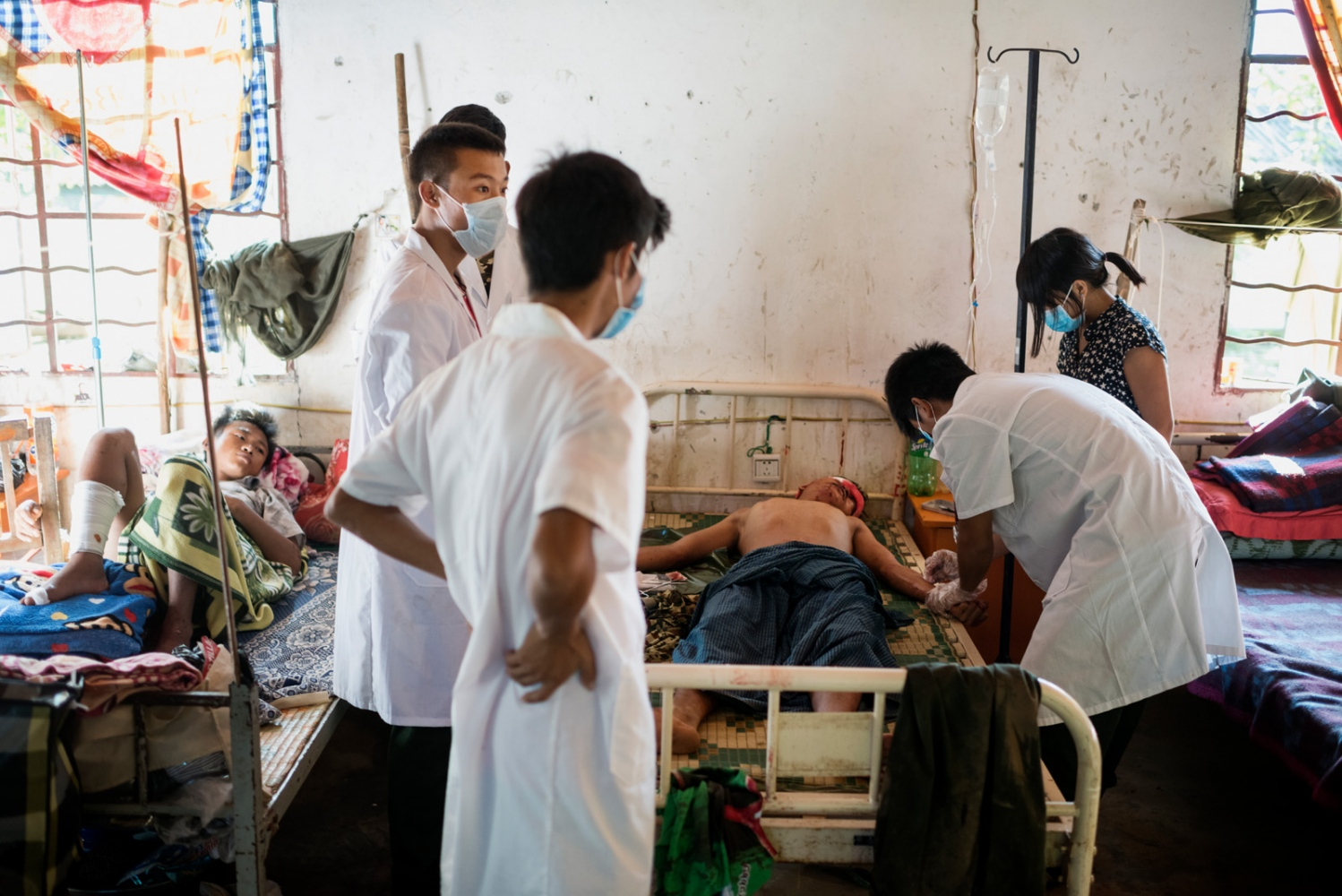 Lazum Htoi San, a K.I.A. rebell injured in a Burmese army shelling of Tsin Yu Bum, a mountain top with a frontline outpost, getting emergency treatment at the army hospital in Laiza, Kachin State, Myanmar.