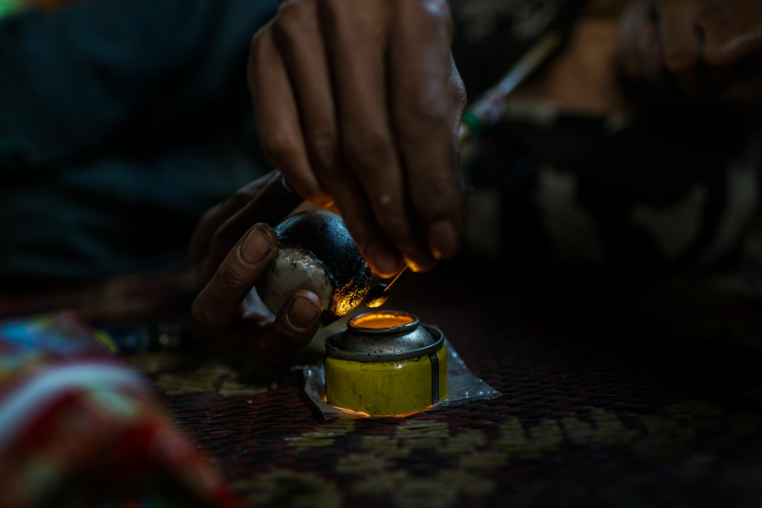 In a neighboring village to the opium farmers the usage of opium is widespread. An active user demonstrates his pipe, lying on the floor lighting it over a small candle.
