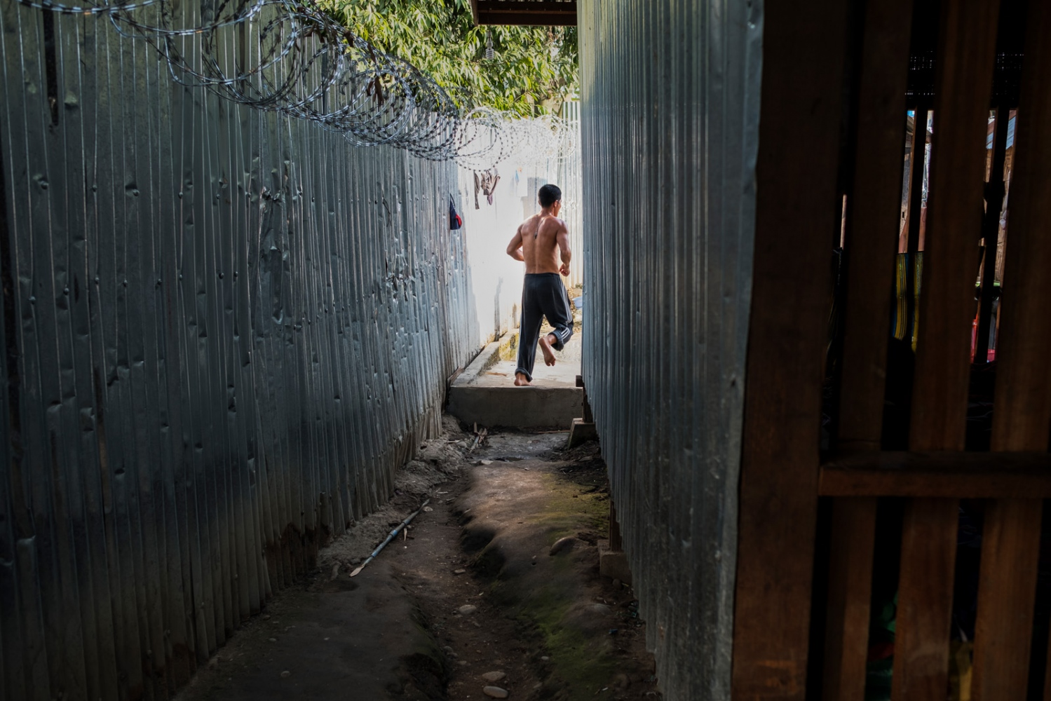 A client runs through an alley with barbed wire fencing at a Pat Jasan drug rehabilitation center in Myitkyina, Kachin state, Myanmar.