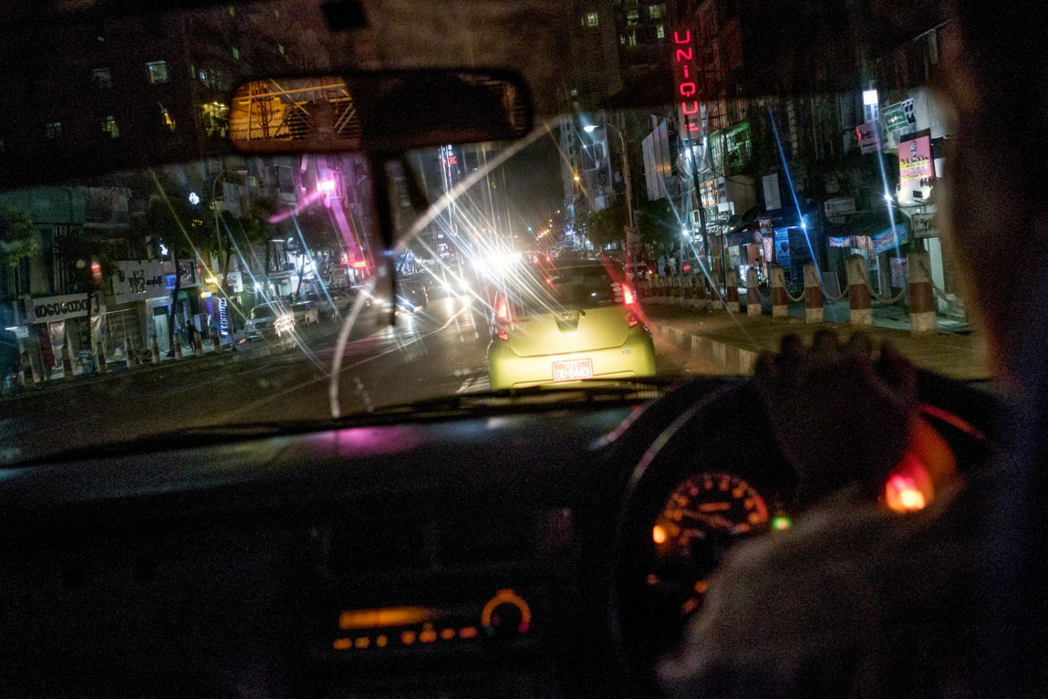 A taxi drives through the night in Yangon, Myanmar,