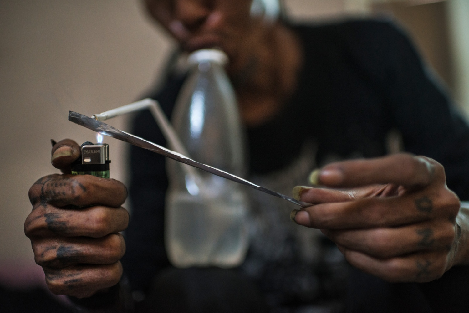A man addicted to both heroin and methamphetamine smoking his afternoon fix of meth in his home in Yangon, Myanmar.