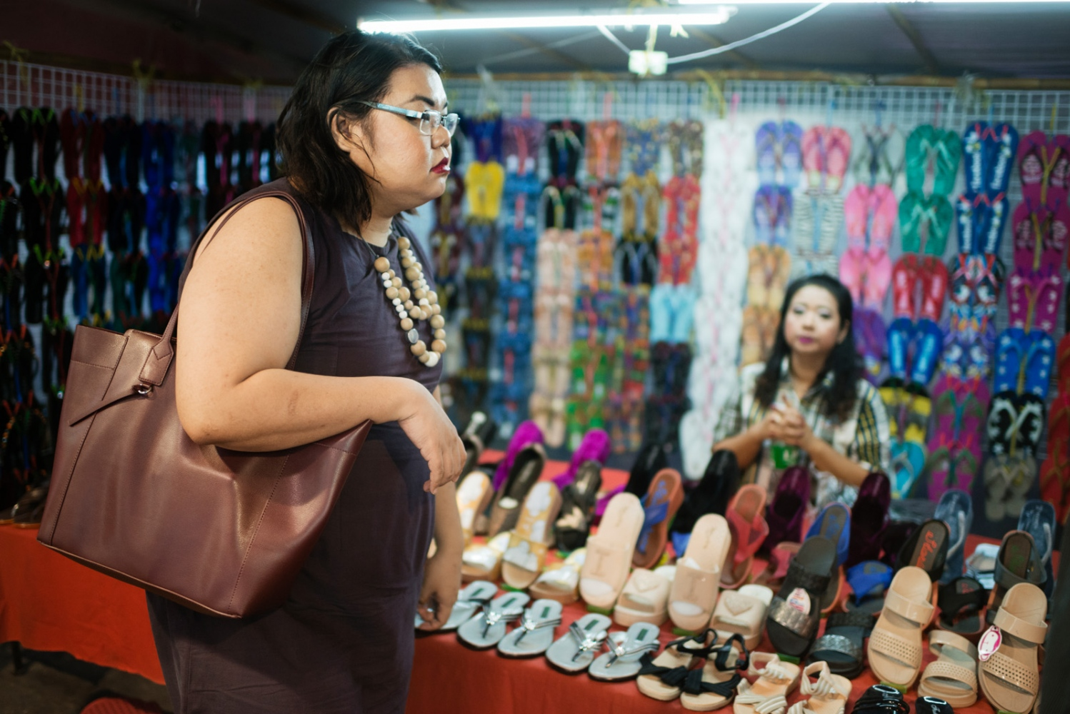 Yaya looking at shoes on a shopping street in central Yangon.