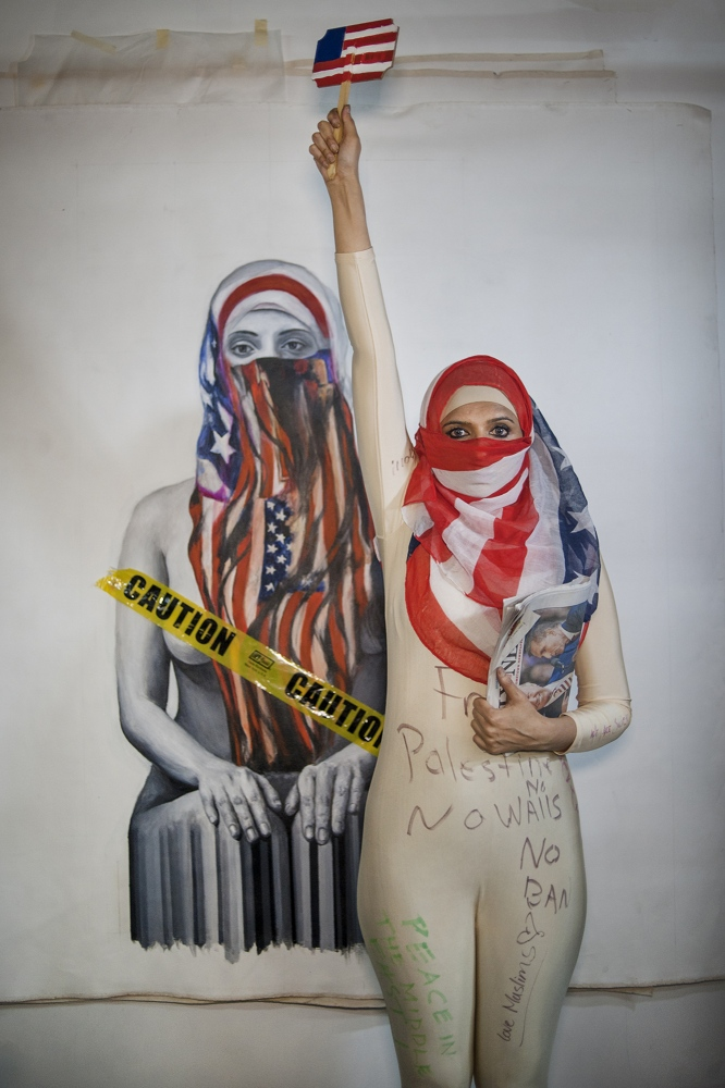 """Qinza Najm is a Pakistani American painter known for bodies of work such as """"Islamic Graffiti"""" and large scale paintings of Muslim women wearing hijabs. Her work has been exhibited at Dubai's Christie's Art, Miami Art Basel, and Sikka Art Dubai. On Valentine's Day 2017, Najm held a fashion show at White Box NYC gallery responding to President Trump's travel ban. She and models from each of the seven Muslim nations affected walked the runway posing as Statues of Liberty in hijabs. Najm said she is still extremely disturbed and trying to """"accept reality"""" in U.S. politics. But she also said there is a positive: more people are getting united. """"At the fashion show, people couldn't stop clapping -- they were crying. I was here during September 11th, and everyone had said 'Muslims are bad.' Here, they had so much empathy. When they were writing comments on the bodysuits, they were writing on the souls of Muslim people, saying 'We are standing next to you.'"""""""