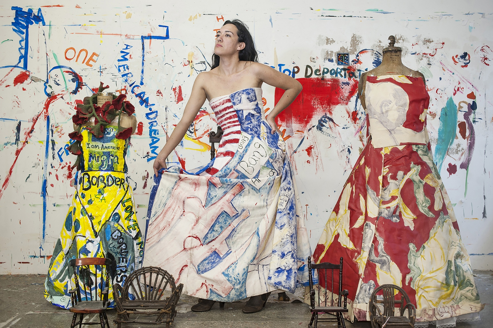 """Maria De Los Angeles is a Mexican American painter recognized for her painted dresses, which are wearable portraits of human displacement and the immigrant experience. Educated at Pratt and Yale, she is an undocumented immigrant smuggled across the border to California when she was eleven. She could not vote in this election due to her DACA status but said she would have voted for Bernie Sanders. She got her DACA status renewed for two more years in July. She has been making dresses since around February 2016, the beginning of the election campaign, interested in the confrontational aspect of wearing stereotypes on one's body. She uses acrylics, painting abstract scenes of migration to look like landscapes, or at other times writing overt commentary on deportation. """"I wanted to create a more nuanced portrait of immigrants,"""" she said. """"And also place myself in my work."""""""