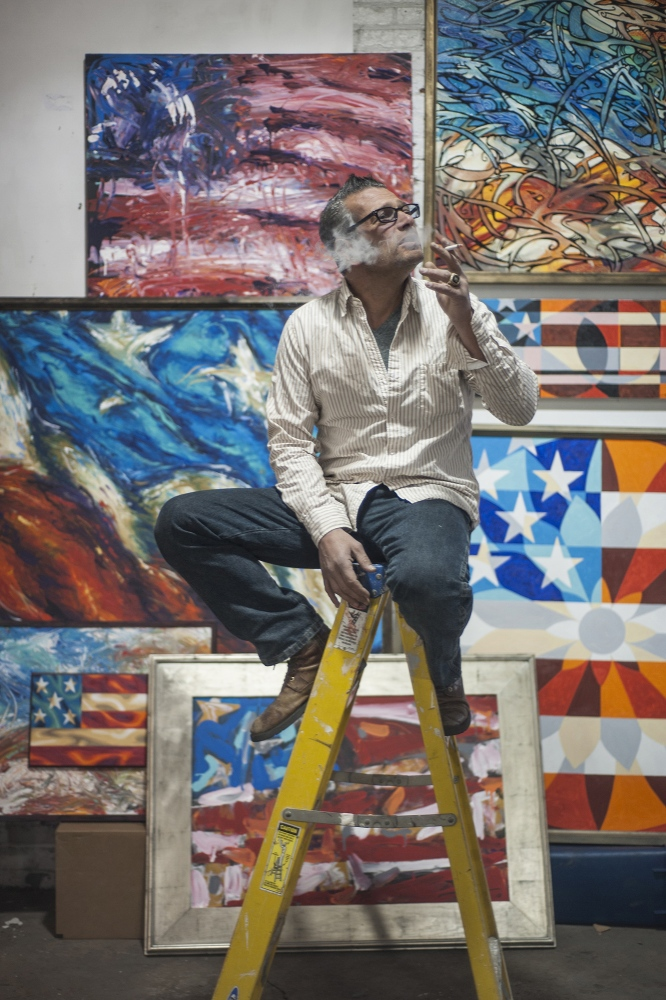 """Scott LoBaido is a painter from Staten Island who makes large-scale renditions of the American flag and abstractions of patriotic symbols. He has toured all 50 states, painting a giant flag in each state to commemorate U.S. veterans. He is also known for his vocal support for Trump in the 2016 election. As a result of his political beliefs, he said he has long been an outsider in the art world. He also said other artists who voted for Trump are wary of the media. Through his art, LoBaido communicates the romance of American nationalism that he believes has been entrenched in negativity. He says his art is for the """"deplorables – those who support Trump, work hard, and don't have time for fancy hoity-toity art."""" Being American should be something to be proud of, according to LoBaido. """"We're not perfect, but we're the best there is. You come here and you struggle, you know? I think that's sexy."""""""