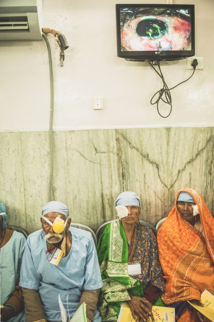 Ganpot and patients wait inside the surgical theatre. Operations in progress are shown on the video screen above while tennis balls are used to hold gauze over the numbed eye.