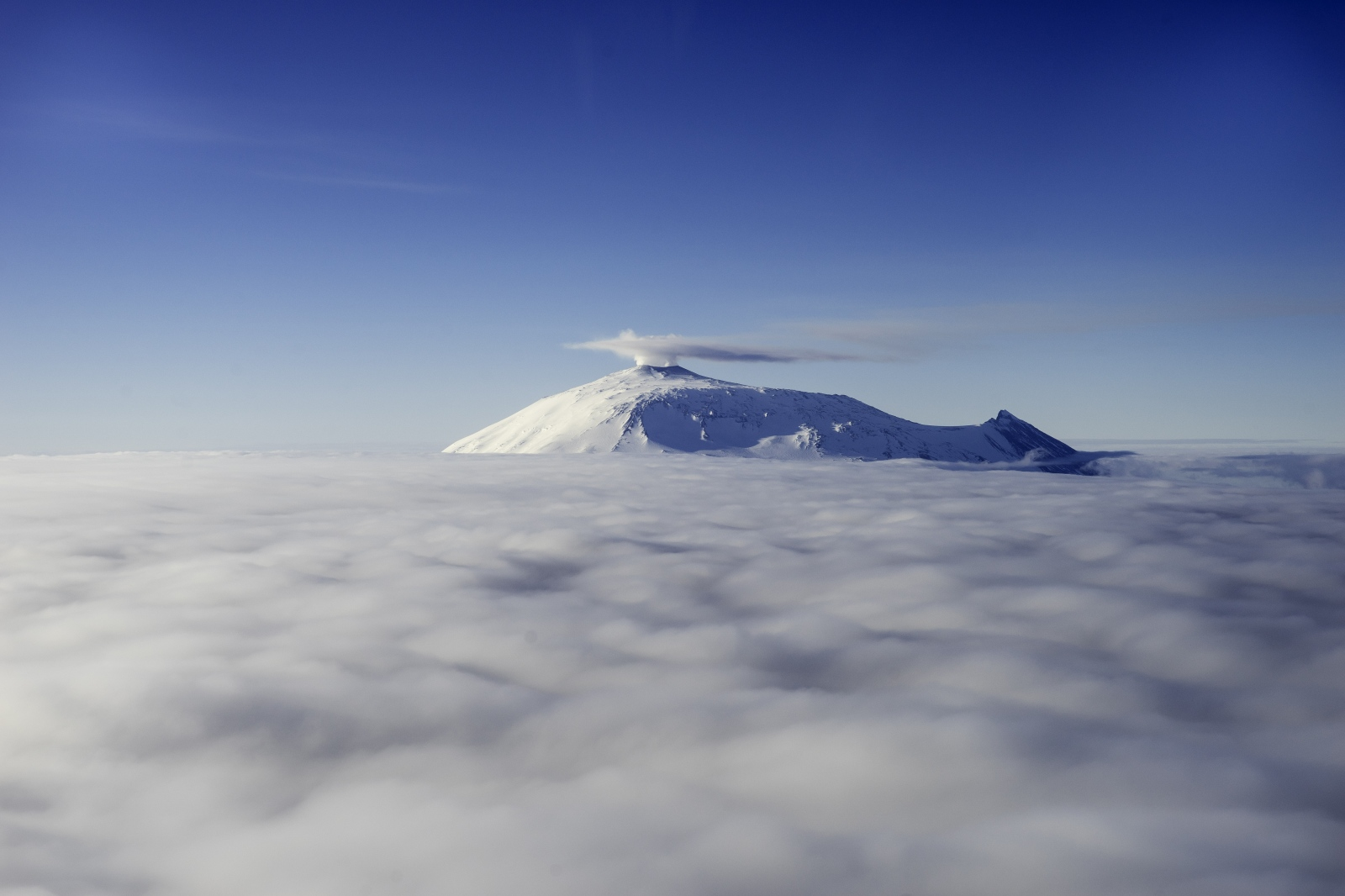10 December 2016. Mt Erebus emerging from the clouds. Viewed from Bell 212 helicopter at 10,000 feet elevation. Erebus is one of only a handful of active volcanos in the world which has an open lava lake. For this reason, and its relative ease of access, due to American and New Zealand science bases nearby, it is one of the most studied volcanos of its kind. The steam coming from its main crater is released 24/7/365. But only on days when the relative humidity and winds are correct, does it appear visible in such a way.