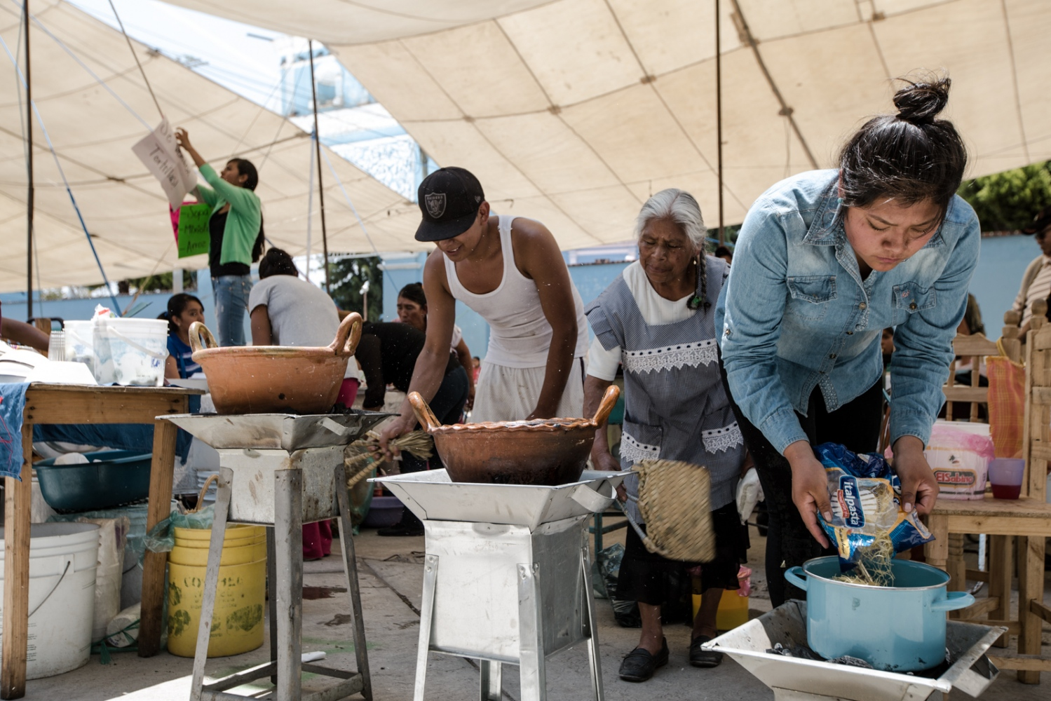 May, 2017. Los Reyes Tlanechicolpan An elder woman and her grandchildren in the preparation of some homemade food, these dishes are typical from the region of Puebla and Cholula. Variations of rice, mole and broth are common.