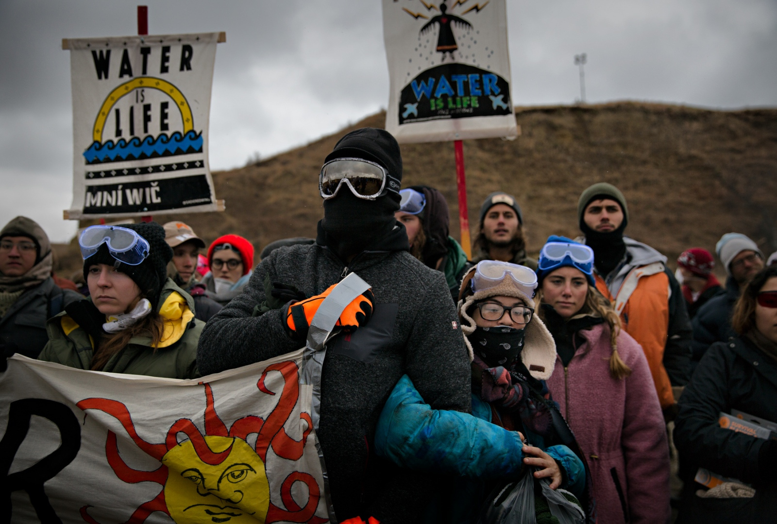 Water protectors confront the law enforcement directive to leave the area and not cross the river to Turtle Island. The law enforcement which was stationed atop of the hill on Turtile Island demanded protectors to leave. Turtle Island is considered sacred ground and the native americans simply wanted access to the Island so that they may engage in ritual prayers.