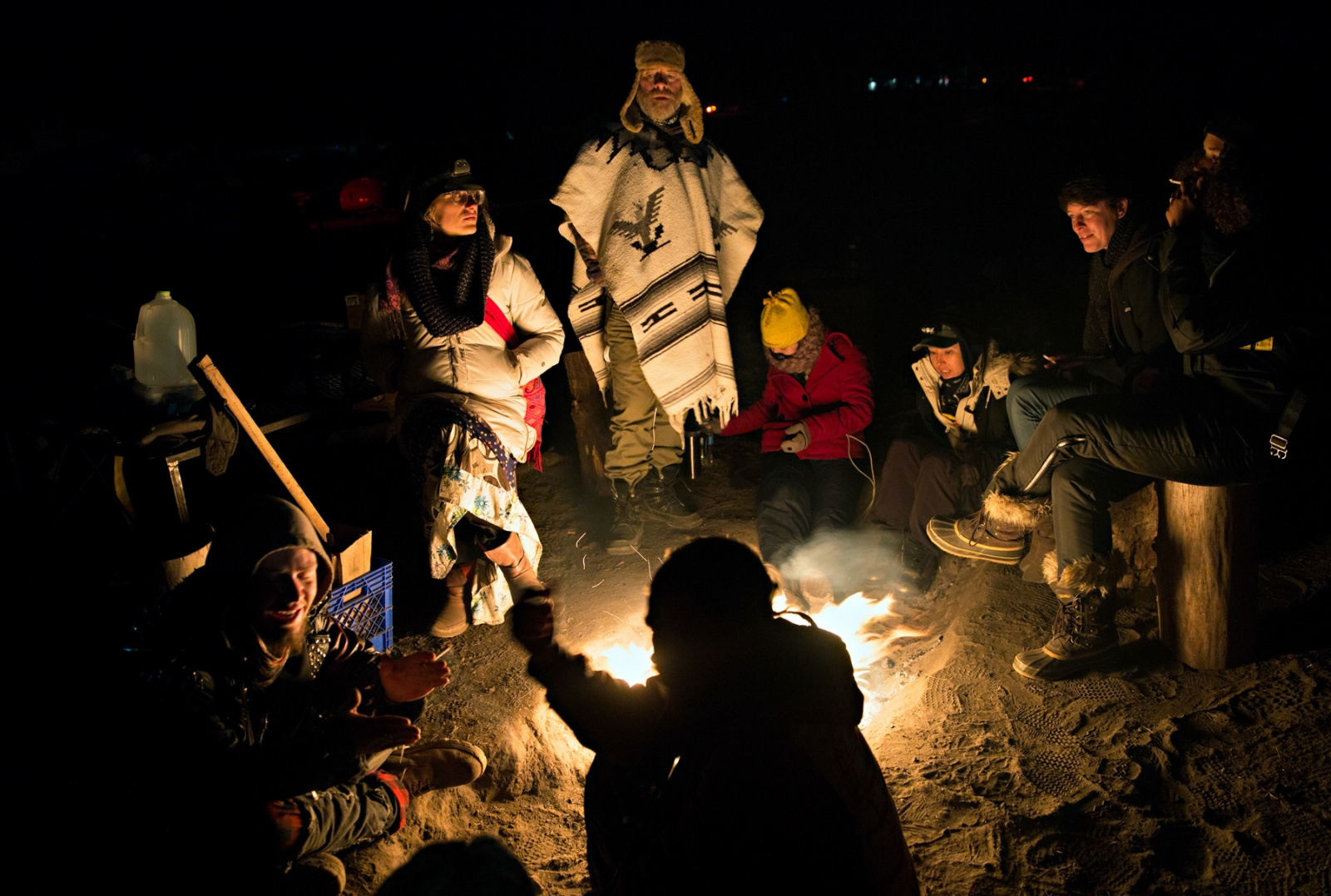A group of volunteers gather around a camp fire singing and telling stories. At night, individual camps would be lit up by camp fires from the donated wood available for everyone's use. Many camps would welcome strangers to sit and enjoy the warmth of the camp fire and share in the meals they had prepared.