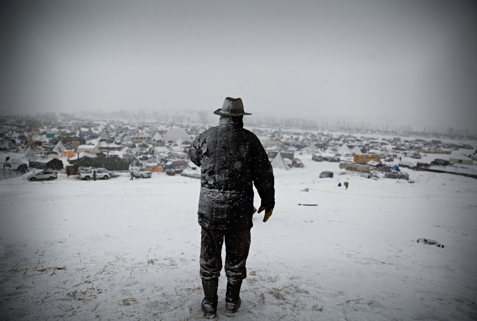 A man overlooks the Camp during a heavy snow blizzard on a December morning when US Military veterans joined the Protectors at the Oceti Sakowin Camp. The veterans had vowed to provide a line of defense against the military style actions of the local and federal law enforcement that had surrounded the Camp.