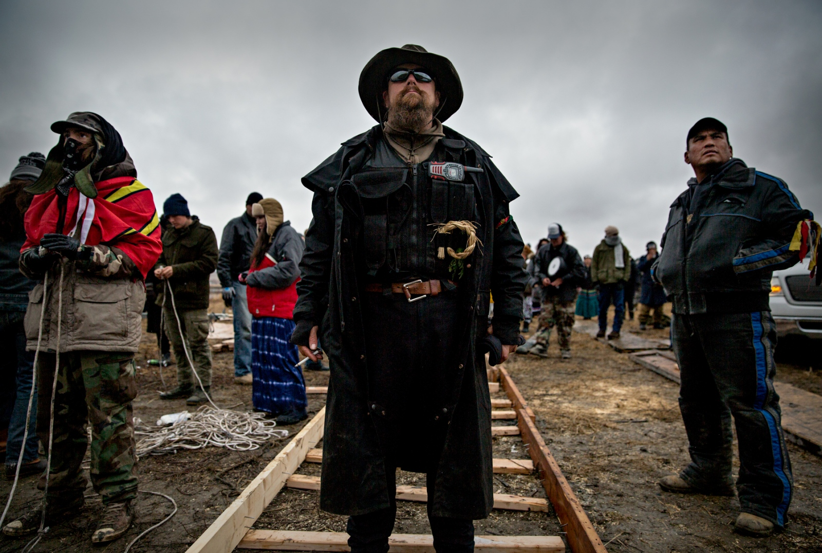 "Adoneus Bishop of Elgon Washington, has been in the Camp for 10 weeks and is member of the Oceti Sakowin Group. He says: ""I am not going anywhere."" The Common Man's Society of the Oceti Sakowin Camp at Standing Rock, ND, is a group of men and women who Serve, Protect, And Tend to the well being of camp."