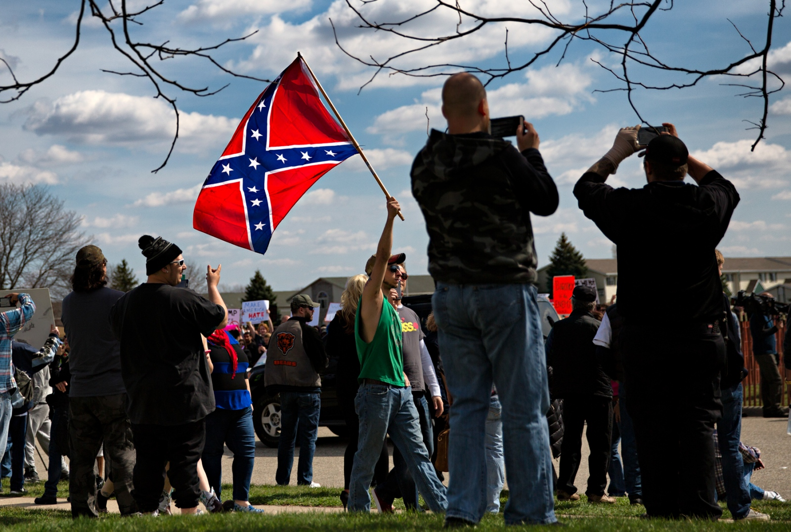 March 29, 2016 - Janesville, Wisconsin - Supporters of Donald Trump waive a confederate flag in the face of the protestors in Janesville, Wisconsin where Trump held a rally.