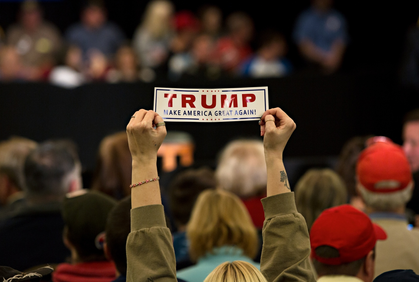 "March 30, 2016 - Appleton, Wisconsin - A supporter of Donald Trump brandishes a Trump bumper sticker during a rally in Appleton, Wisconsin. Trump asked his supporters to turn around and look at the ""lying media"" while he berated the media's coverage if his presidential run. He criticized the media for not interviewing his supporters and only covering negative news about him."