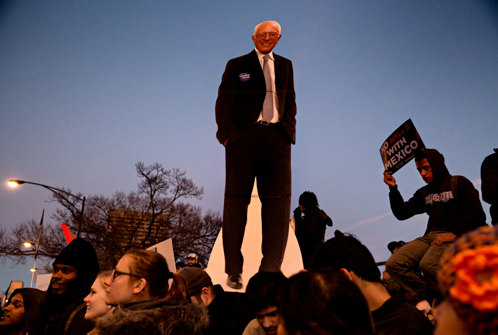 March 11, 2016 - Chicago, Illinois - Chicago protestors brandish signs and a cardboard cutout of Bernie Sanders in front of the University of Illinois's Pavilion where Donald Trump had scheduled an appearance. Due to the intensity of the protests and the UIC student's infiltration of the Pavilion, concerned about his security Trump cancelled his appearance.