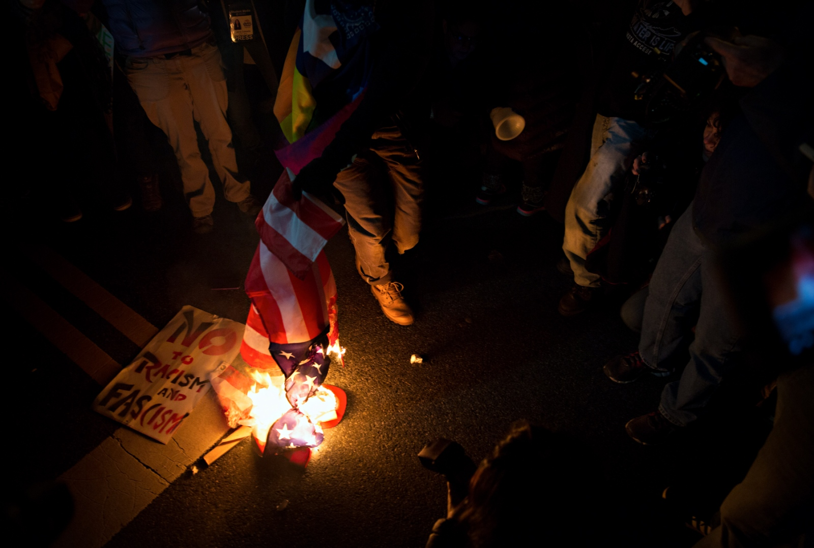January 19, 2017 - Washington, DC - The anti-Trump protestors voiced their anger about the election of Donald Trump by burning a US flag during one of the many protests that lasted all day and night the day before the Inauguration.
