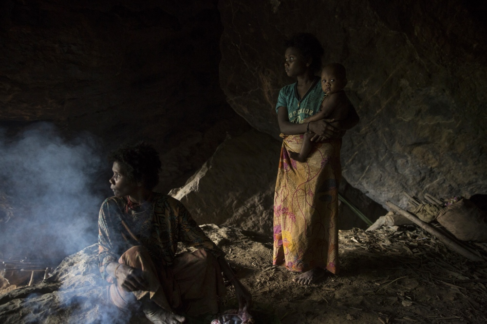 A mother and child stand in a cave. During the rainy season groups search out caves deep in the forest where they will stay until the rains stop. Satun - July 2017