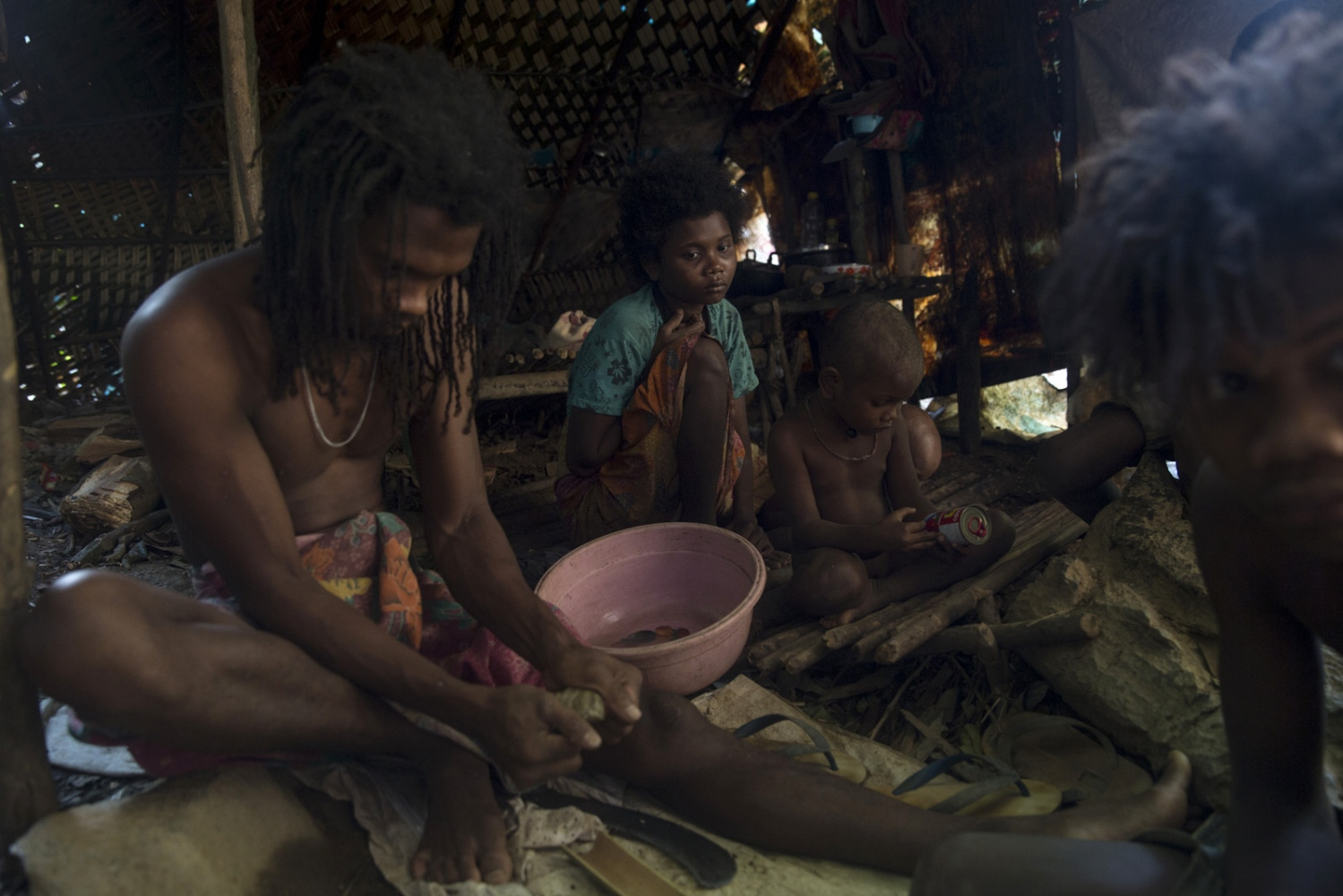 A family group sit in their shelter whilst Ja (left) moulds a natural resin to fix his blowpipe.  Satun - July 2017