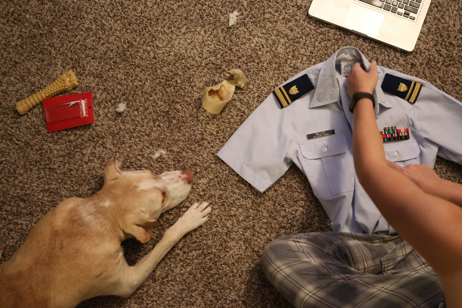 Taylor prepares her uniform the night before her promotion ceremony while her dog, Sunny, dutifully lies at her side in Long Beach, Calif on January 8, 2017.