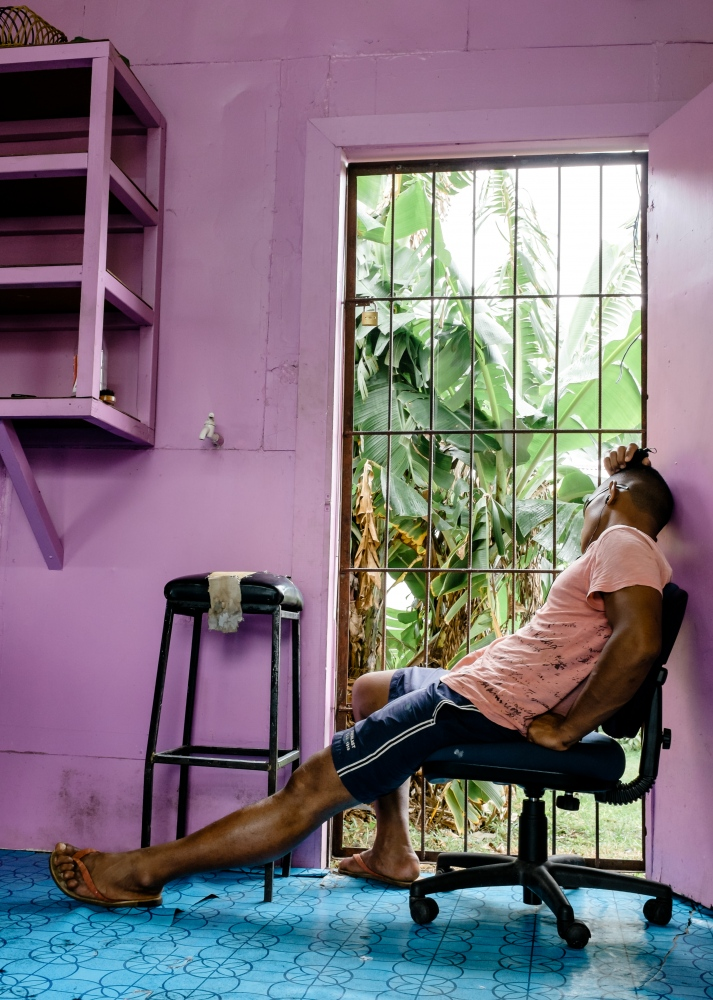 A barber takes a mid day nap at his shop in...