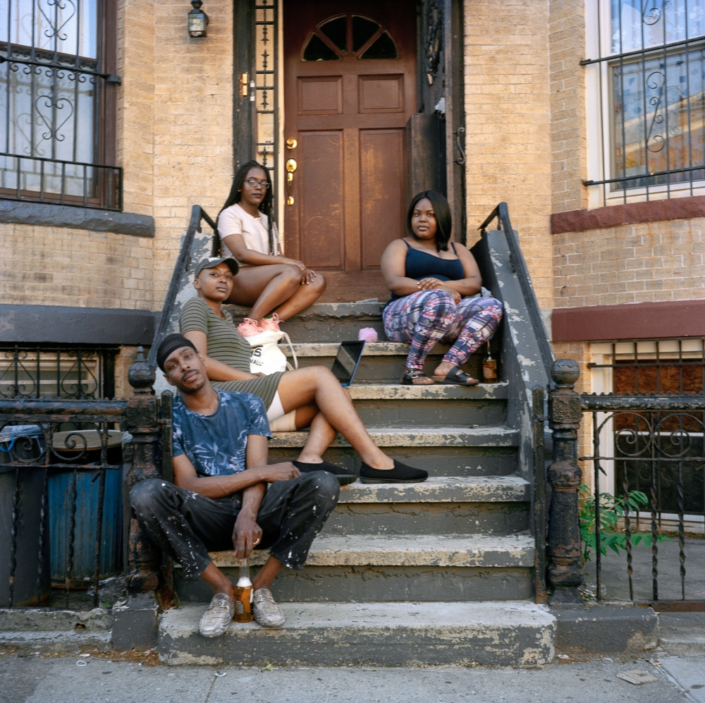 May 17, 2017 - Brooklyn, New York City, NY, USA - Schenectady Avenue between Park Place and Sterling Place. From left to right: Osman is half Venezuelan an half from Granada, he is the cousin of the twins. Khyana, 23 years old, was born and raised on Schenectady Avenue and is best friends with the twins. The twins, Makaya and Makayda McNeilly, 19 years old, from Granada and raised in the house in the background. For Makaya, change in the neighborhood means new people moving in, rent prices going up, and seeing her family and friends leave the neighborhood because they can't afford rent.