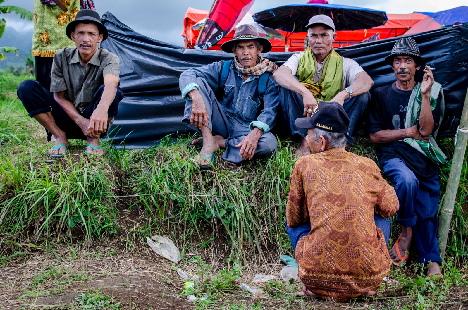Indonesians are highly social and Pacu Jawi allows not only for fascinating sport, but also community time. Here, a group of men have gathered, awaiting the start of the races. There is much conversation, whether scoping out the contenders, or just catching up with friends. Prepared for a long day out in the sun, the men are wearing unique headwear.