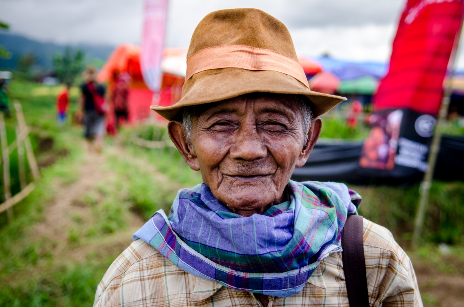 People come from many villages within the area to watch the races at Pacu Jawi. The location shifts kampungs (neighborhoods) each harvest season, using a partially drained paddy for the races, which incidentally helps to turn the soil before planting the next seasons seeds. This older Indonesian man has come to watch the skilled jockeys and powerful bulls, mingle with friends and family and, likely, place a couple of bets along the way. The all day event prompts appropriate sun protection, both hats and scarves, as the spectators are fully exposed in the middle of a field just south of Mount Marapi in West Sumatra, Indonesia.