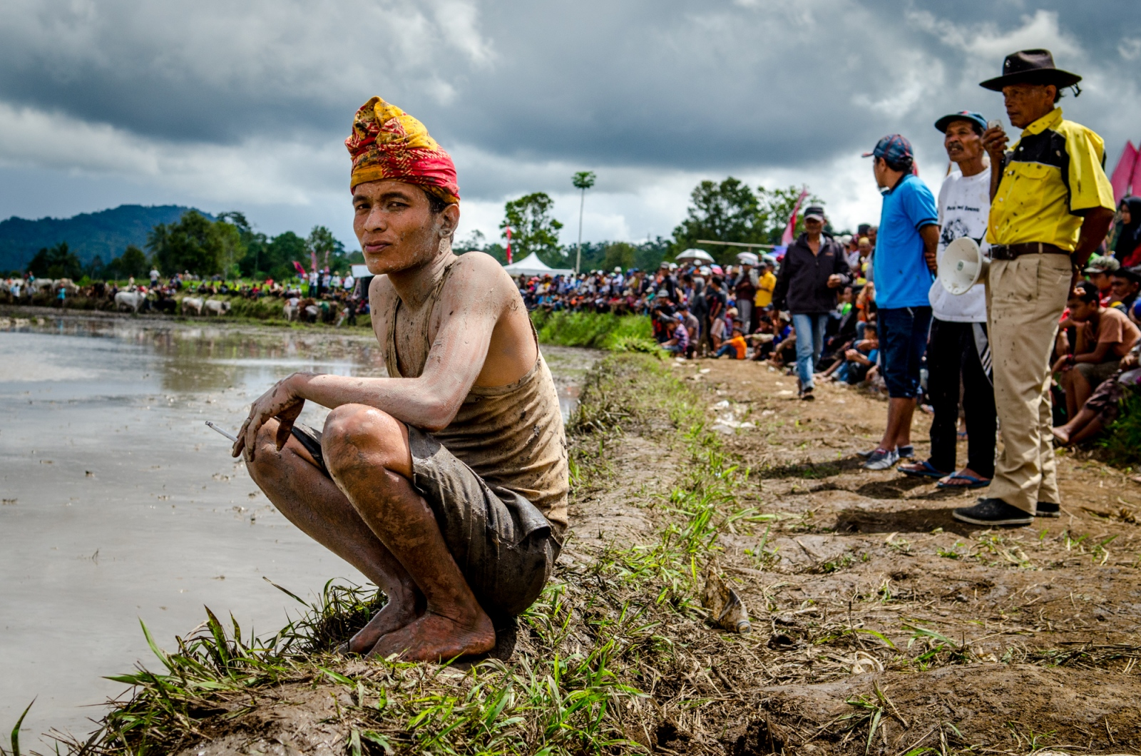 A muddy jockey relaxes with a cigarette between rounds, resting his muscles, catching his breath and taking in the sights. Perched alongside the rice paddy where the races are taking place, this young man must be well aware of his surroundings and ready to jump out of the way if any bulls decide to bolt over the ledge. When a pair of bulls arrive to the starting line in need of a jockey, he will mount back off to race down the track he sits in front of.