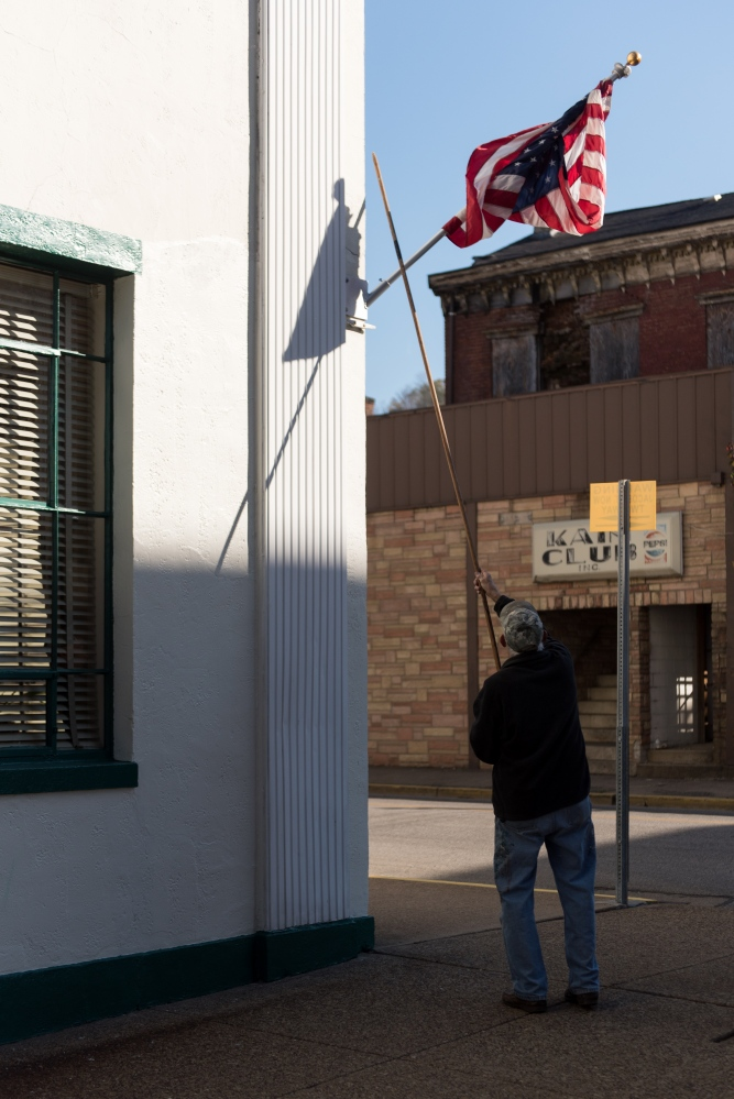 Mel Joseph, a lifelong Wheeling resident, attempts to straighten out a tangled American flag outside of Kepner Funeral Home in South Wheeling. Joseph and his friend Bob Carl, also a lifelong resident, perform general maintenance for the chain of funeral homes, one of the few old family-owned businesses that has persisted in Wheeling.