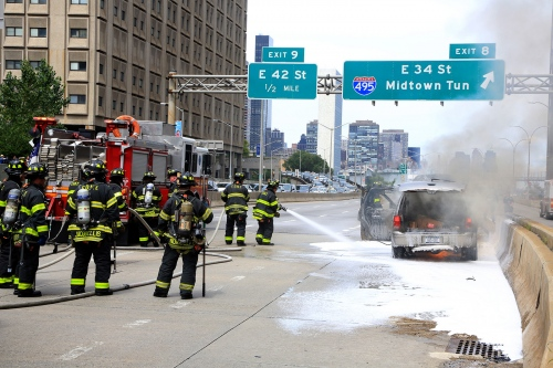 Firefighters extinguish a fire on a car at FDR Drive near East 34th Street in Manhattan.