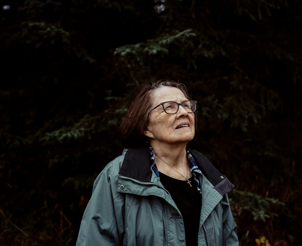 "Clare Swan, 85, outside of her home in Kenai Alaska. Swan, who is Kenaitze, says that there is a connection between loss of language and culture and loss of land due to climate change. ""Of,"" she says. ""Our language comes from the land."""