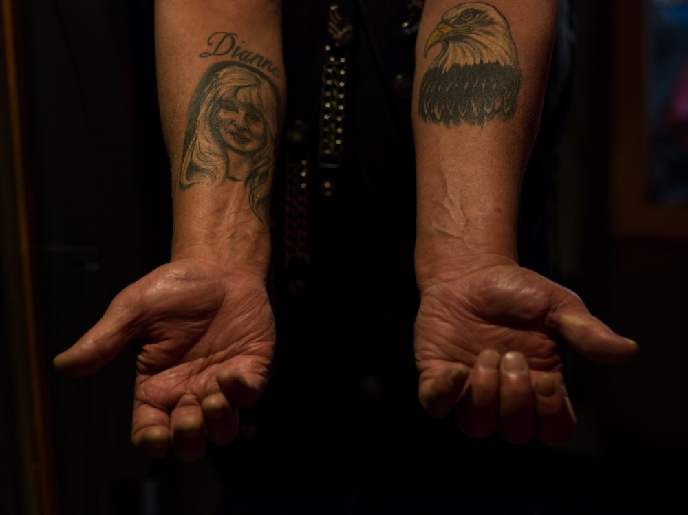 "Richard Crook displays two of his tatoos; his wife of almost 48 years on his right arm, and a bald eagle on his left. Crook, who served in the navy for 6 years, is currently the chaplain for the American Legion Riders in Anchorage, Alaska. He says that the community of friends he sees reguarly, like on nights like tonight at the American Legion Jack Henry Post 1, are like family to him. ""These are the best people you'd ever want to be associated with,"" he says."