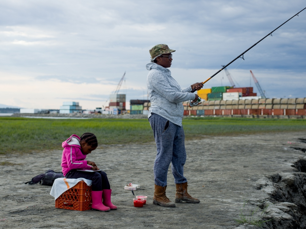 "Cipriana Williams, 32, fishes in the evening at high tide at Ship Creek, with her neice Yukari Williams, 5. She says that there are all kinds of risk in life, especially living in Alaska, like the catastrophic earthquake that hit Anchorage in 1964. ""You live here and you love it, but you know at any moment it could be like '64 and we're out,"" she said. ""It's just like a shake of the dice, I guess."""