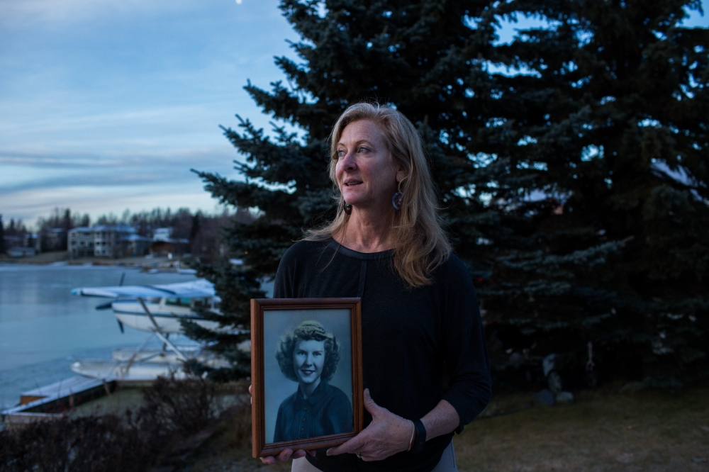 Rhonda Scott holds a portrait of her mother, outside of her home on Cambell Lake in Anchorage, Alaska. Scott's mother passed after a struggle with Alzheimer's.