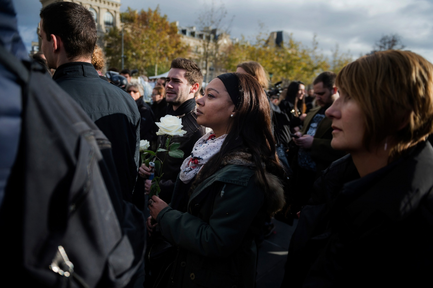 A woman holds a white rose during a silent minute at Place de La République two days after several coordinated terrorist attacks in Paris, France, left over a hundred people dead.
