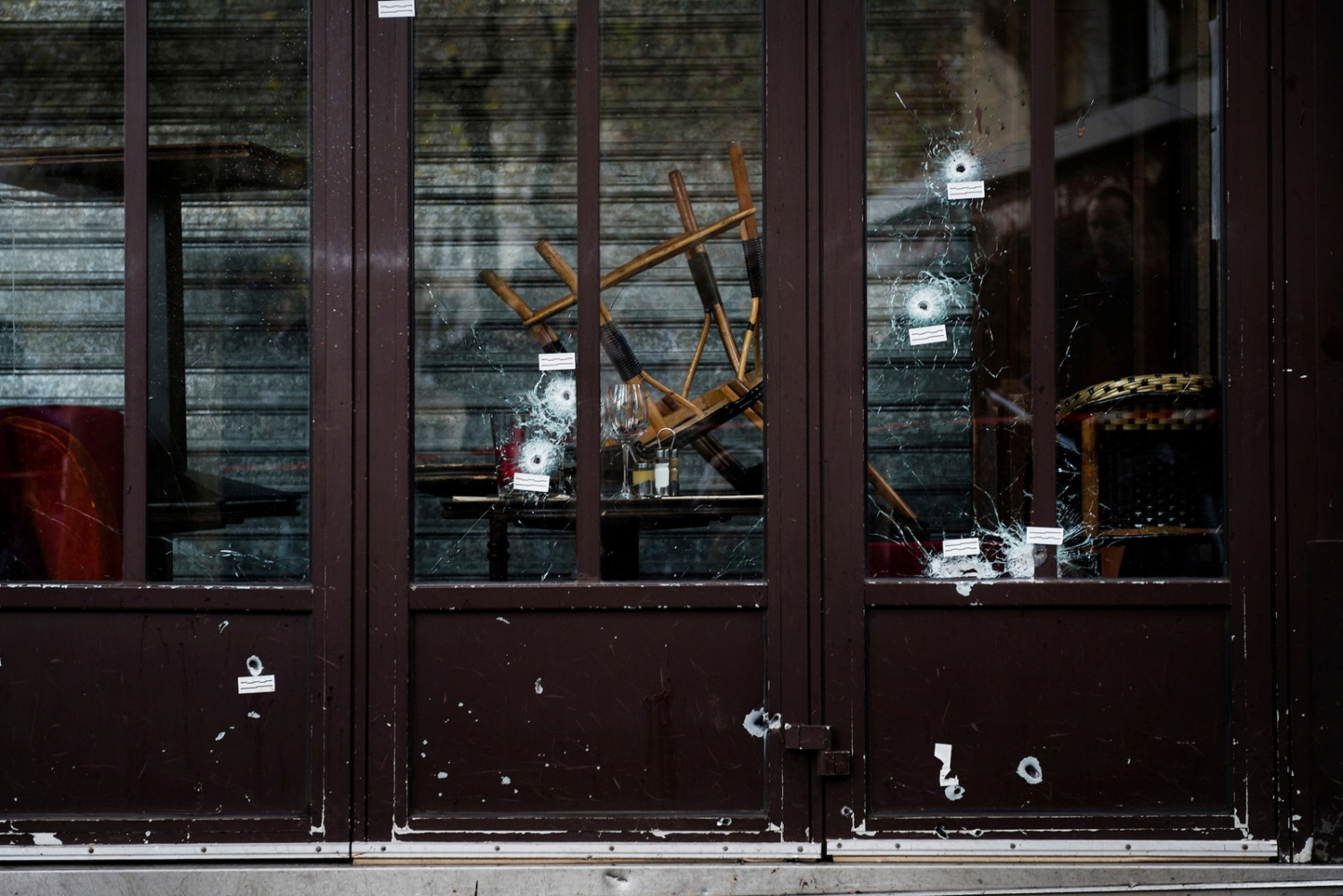 Bullet holes in the windows of one of the restaurants at Rue de la Fontain au Roi, where five people where shot to death in a terrorist attack. Several coordinated terrorist attacks in Paris, France, left over a hundred people dead.