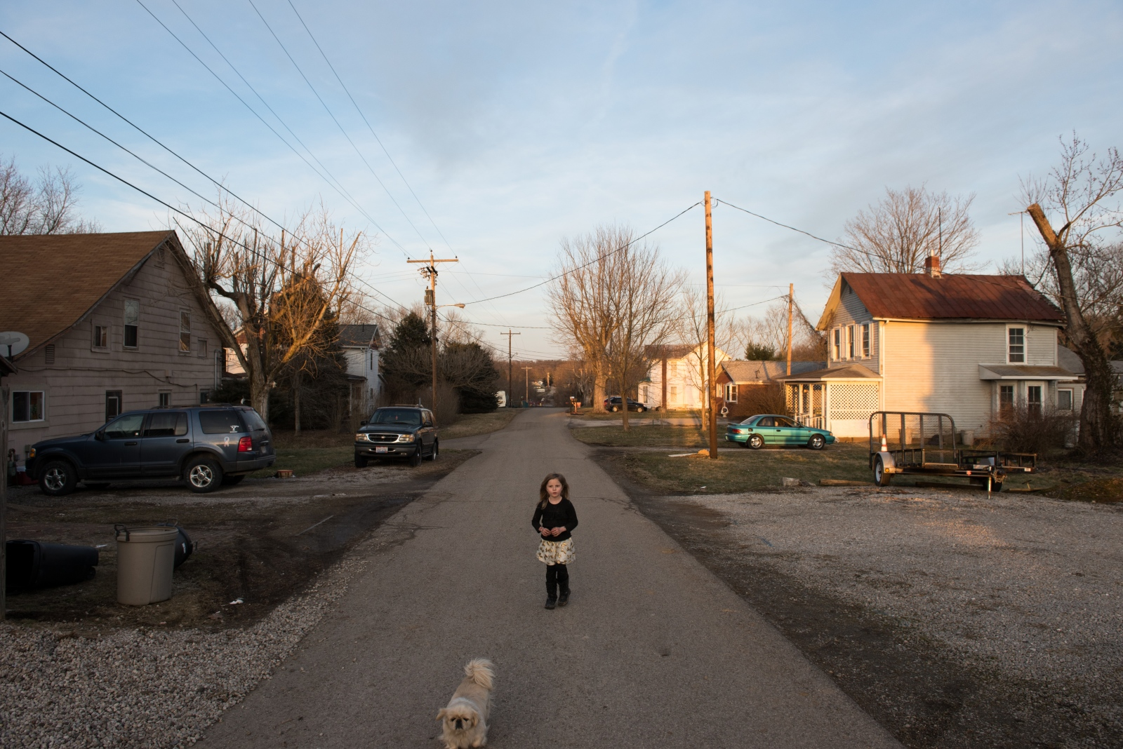 Chloe Harris and her dog walk in the late afternoon light in Coolville, Ohio.