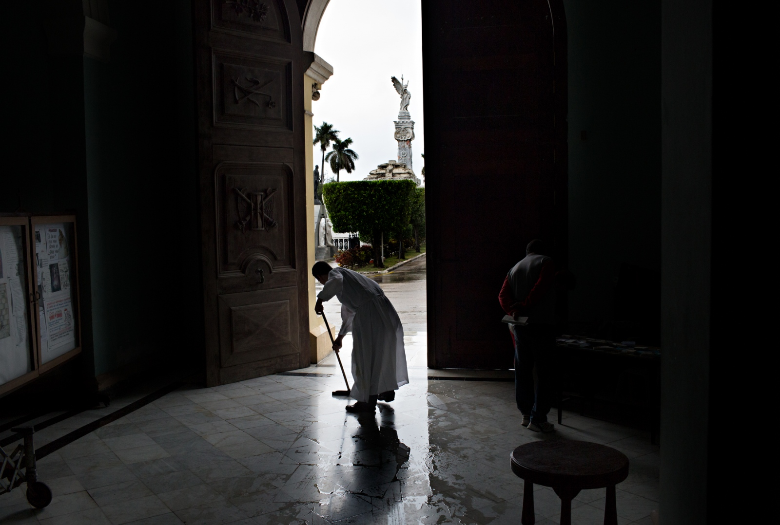 A priest at the Colon Cemetery's parish cleans water parishioners have tracked in before beginning the morning mass. Colon Cemetery is the largest cemetery in Havana.
