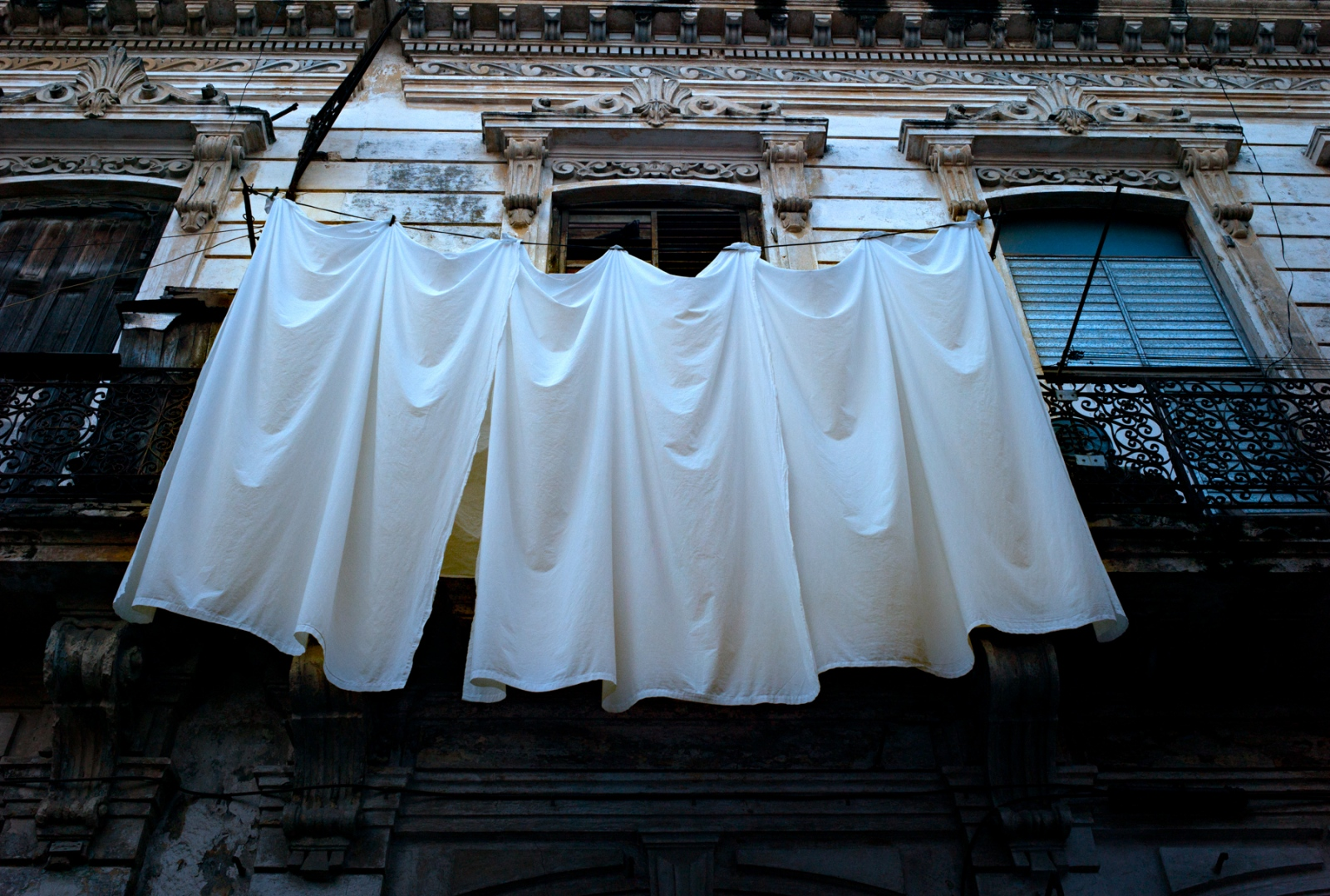 Sheets hung to dry outside of an apartment's window in Havana.