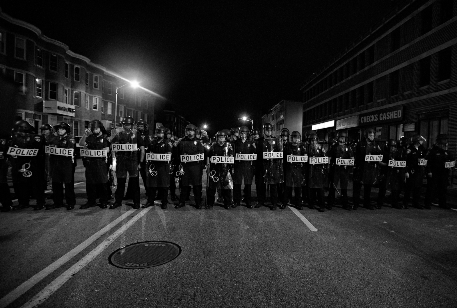Baltimore, MD-Police in riot gear forms a line to impress protestors right before the curfew time while demanding the protesters to go home.