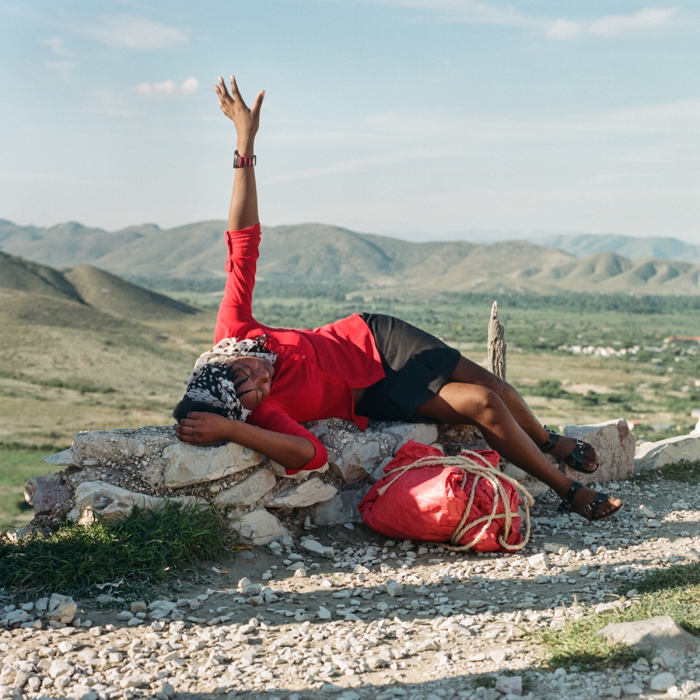 "Ti Pinsik, Aux Poteaux, 4th ""section communale"", Gonaives, Haiti. At the top of peak, a woman prays intensely. The red tarpaulin, rolled at her feet, will be rolled onto the ground so that the faithful can prostrate themselves in the name of their Gods."