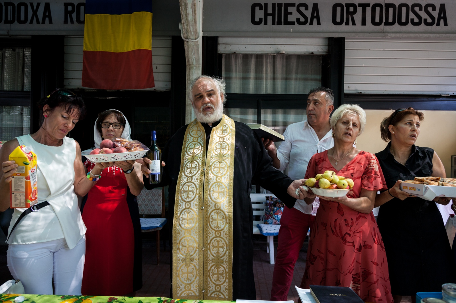 July 30, 2017 - Sunday celebration at the Romanian Orthodox Church in Tor Sapienza, located in a complex of public housing in Tor Sapienza, a working class neighboohood in southeast Rome. Padre Stefano is blessing the food that church members brought.