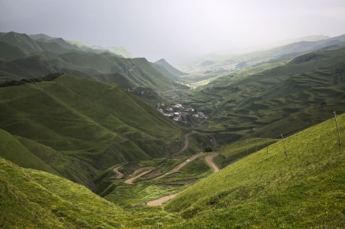 A remote twisty road winds its way through the green hills as rain approaches in the little known Republic of Dagestan, Russia.