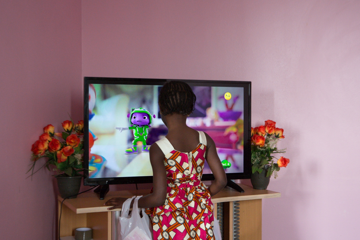 Manchyta watching a cartoon on television. Saint Denis, Ile de France, France