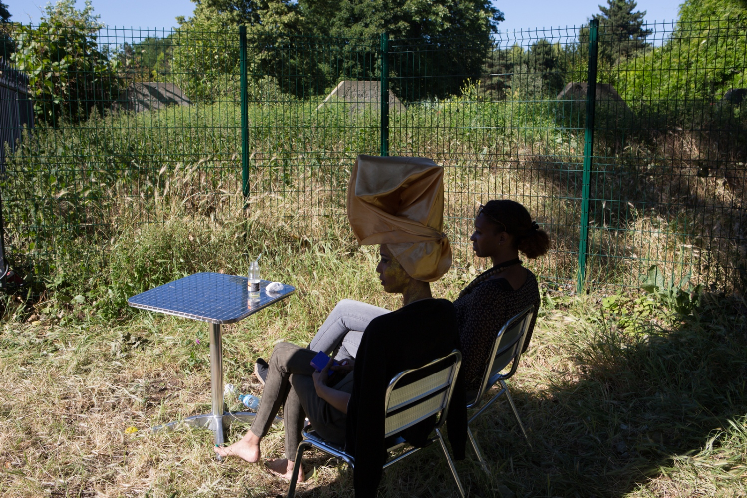 A model and her colleague having a coffee in the Parc Floral garden before preparting to enter the fashion show during the Natural Hair Academy event. Natural Hair Academy is an annual event that turns around beauty and cosmetics to natural Afro hair. Fashion shows, meeting, interventions about emmancipation and feminism are also part of their program. Vincennes, Ile de France, France