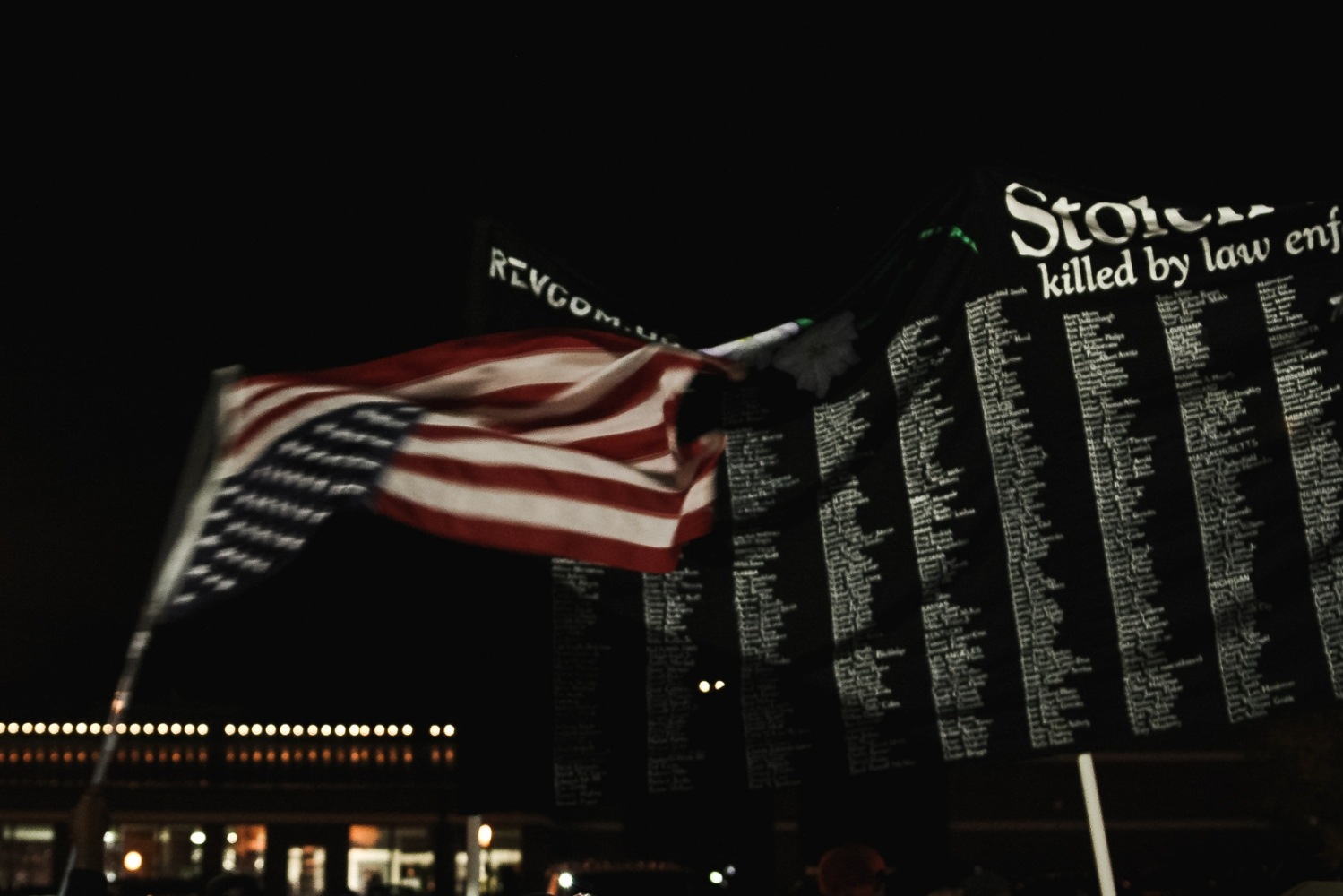 An activist waives an upside down U.S. flag next to a Stolen Lives Project banner that lists each reported individual killed by U.S. law enforcement from 1990 to 2014.