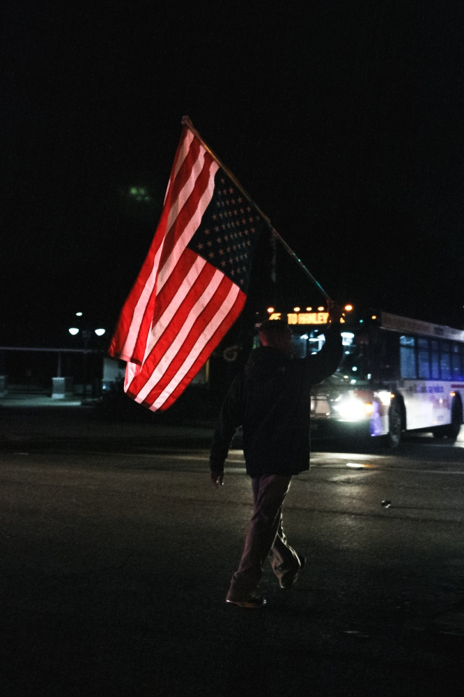 An activist blocks a Ferguson intersection while holding an upside down U.S. flag.