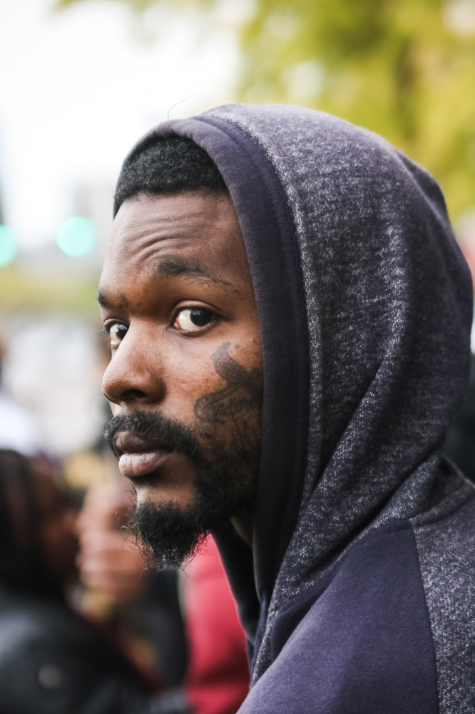 A city resident with a tattoo of the St. Louis Cardinals baseball team logo watches as activists march to the city's police department.