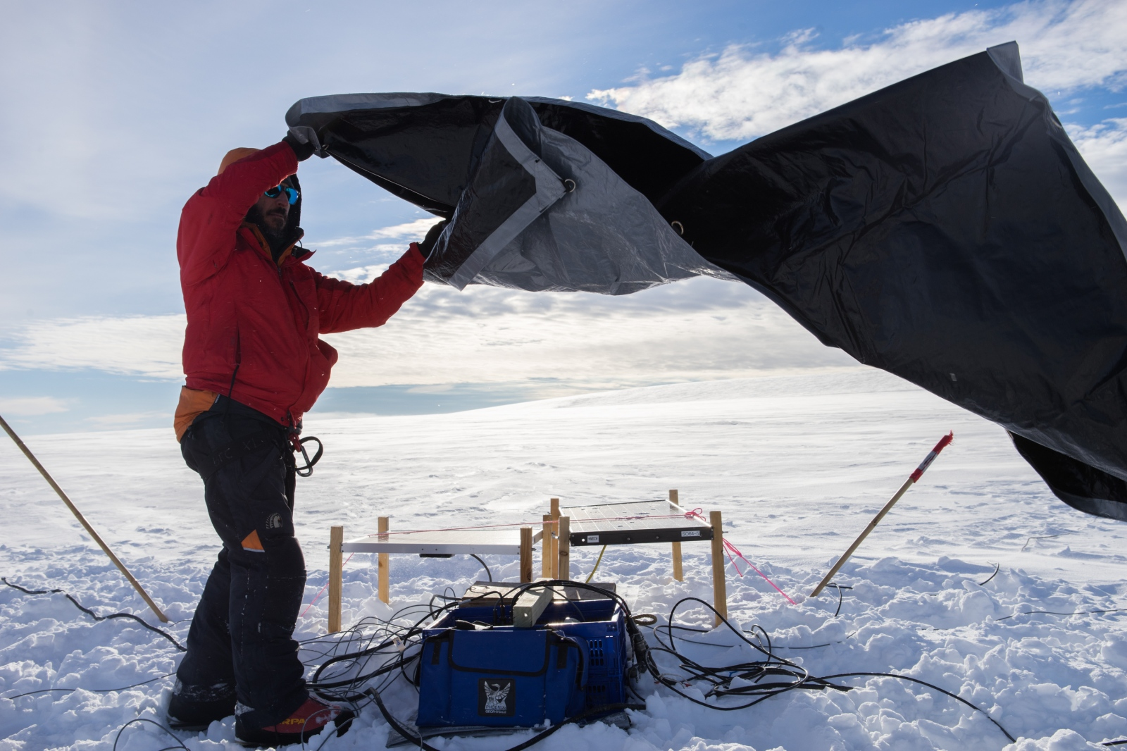 Dr. Paul Bedrosian covers the geophysics equipment before leaving it to sit on the glacier and collect data over a one-week period.
