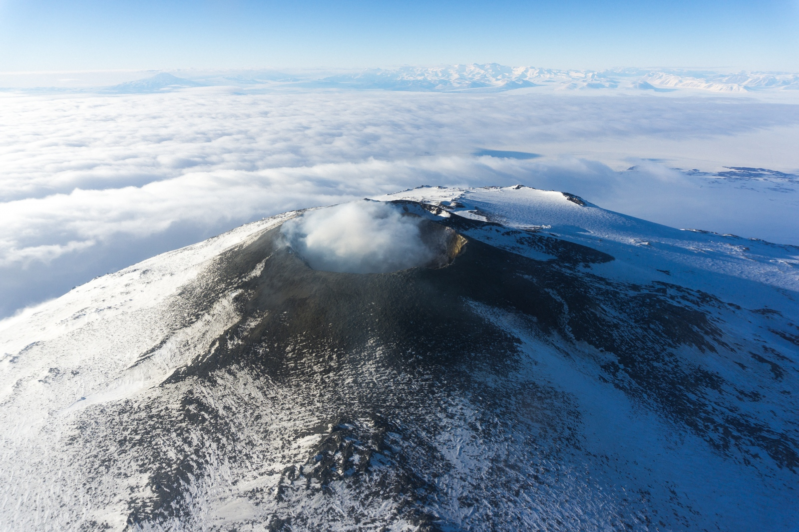 Mt. Erebus (3.700 meters) crater viewed from helicopter. As the southernmost active volcano, Erebus continually emits steam from its molten lava lake a few hundred meters beneath the crater rim. In the background are the transantarctic mountains which span thousands of kilometers and are one of the longest mountain chains in the world.